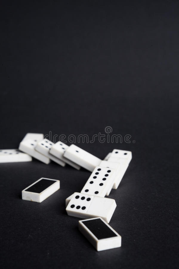 Fallen dominoes domino effect lose fail concept black background royalty free stock image