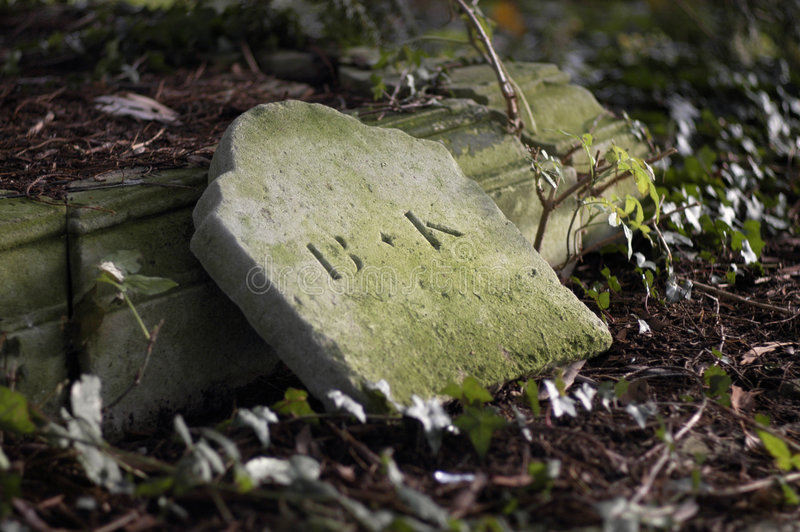 Fallen Headstone. A centuries old tombstone with a faded inscription lying at an angle in a old European cemetry. Shallow DOF, focus on texture of gravestone royalty free stock images