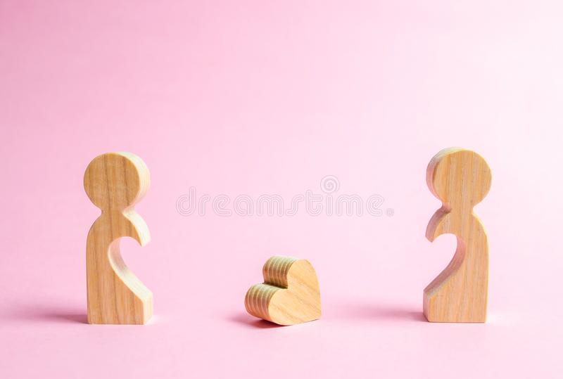 A fallen heart lies between two former lovers. The concept of separation or divorce. Reunion and restoration of love relationships stock photos