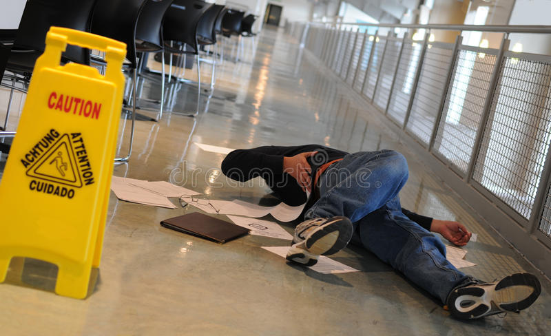 Fallen man. A man who slipped on a wet floor beside a bright yellow caution sign holds his back in pain stock images