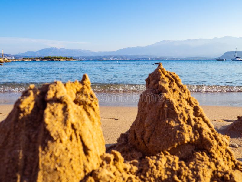 Fallen sand castles - calm sea and a empty beach royalty free stock image