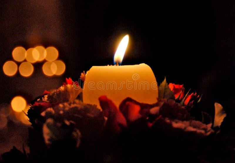 Fallen Schimmer einer Kerze über Blumen in Ohnmacht stockbild