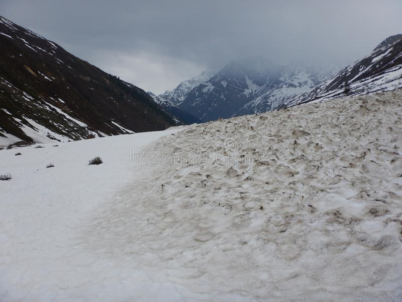 Fallen spring avalanche in an alpine valley stock photography