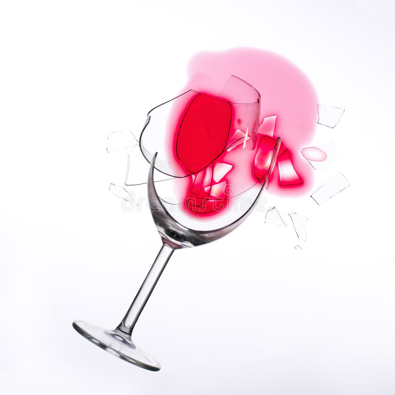 Fallen wine glass. With red wine in it and red stain on a white tablecloth stock images