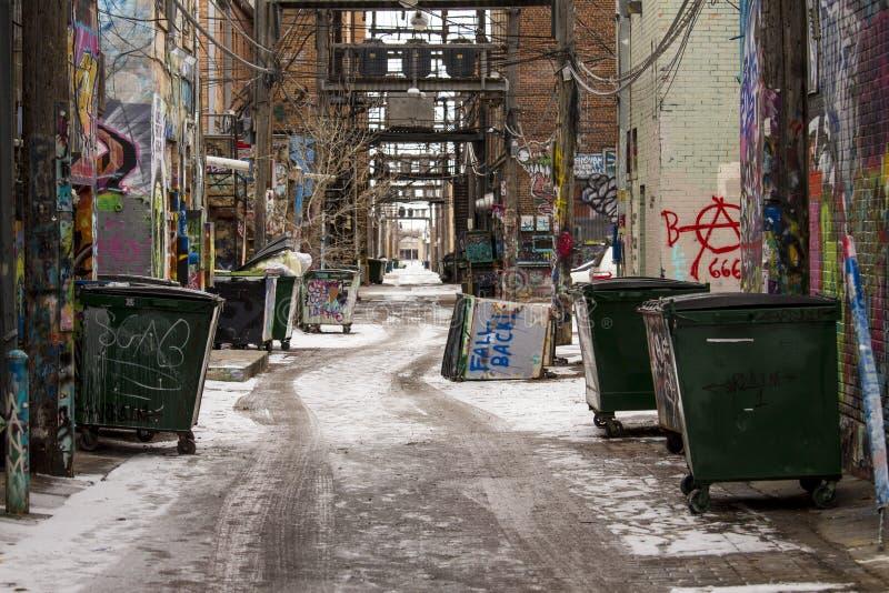 Fallen zurück umgekippter Müllcontainer in der schneebedeckten städtischen Gasse stockfoto