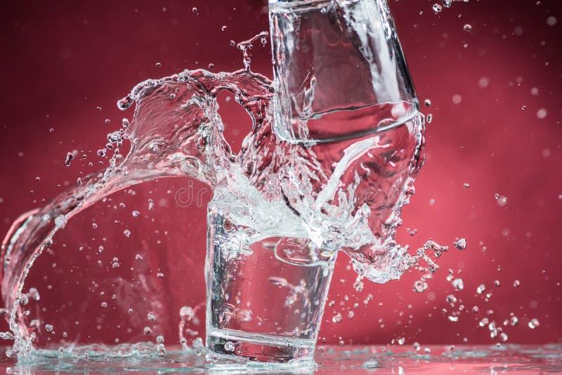 Fallende kleine Gläser und Verschütten des Wassers auf einem blauen Hintergrund lizenzfreie stockbilder