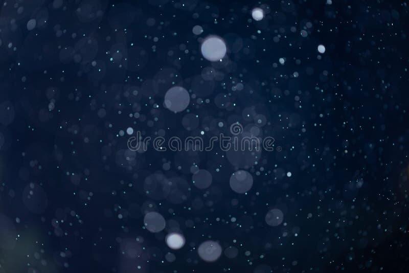 Fallende Schnee oder Regen bokeh Beschaffenheitsüberlagerung auf blauem Hintergrund lizenzfreies stockfoto