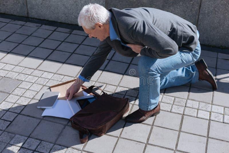 Fallende Tasche des ungeschickten Pensionärs von seiner Hand draußen stockfotos