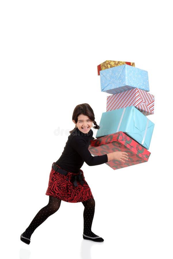 Fallender Stapel des jungen Mädchens der Weihnachtsgeschenke stockbild