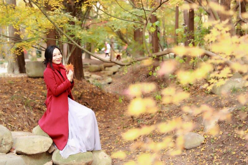 Fallfrau glücklich und Glück, Schönheit, die auf einem Stein im Herbstpark sitzt lizenzfreies stockfoto