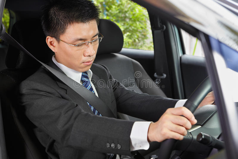 Falling asleep in car. Chinese businessman inside car falling asleep stock photography