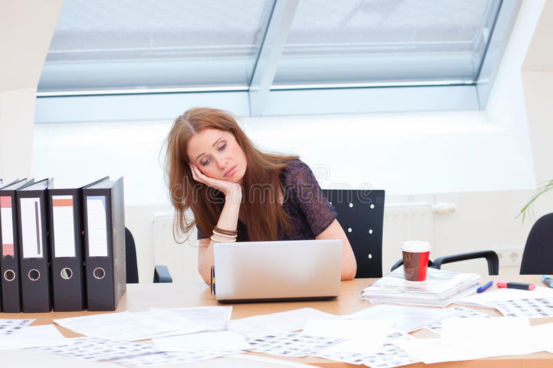 Falling from chair. Bored business woman is almost falling from her chair royalty free stock image