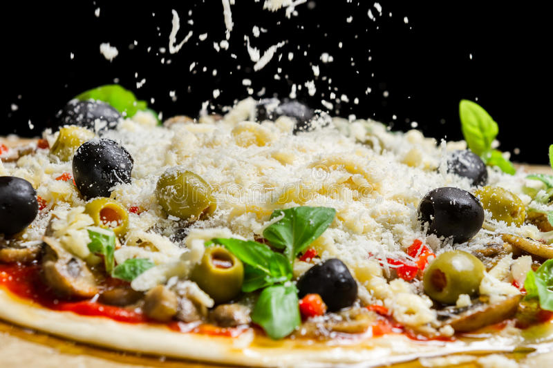 Falling cheese on a freshly prepared pizza stock image