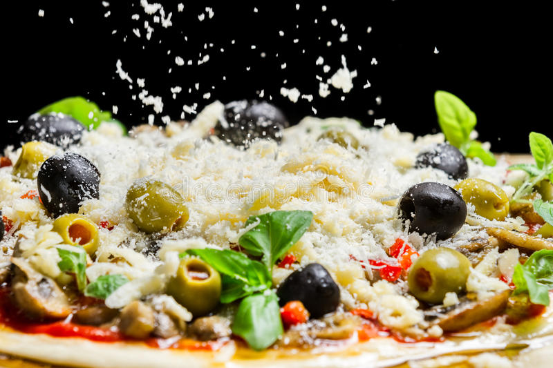 Falling cheese on a freshly prepared pizza royalty free stock image