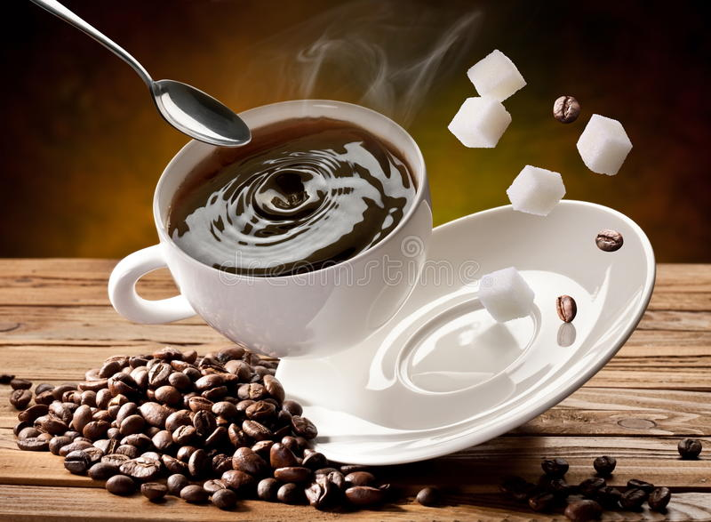 Falling cup coffee. Spoon and sugar cubes are falling down also stock photography