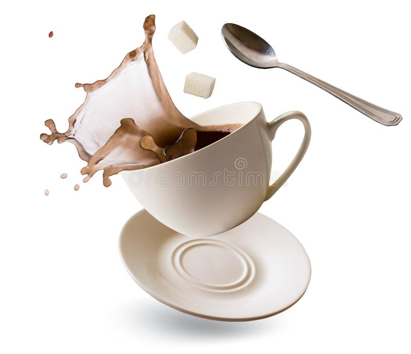 Falling Cup with coffee splash, cubes of refined sugar and teaspoon on a white. Background. Isolated stock images