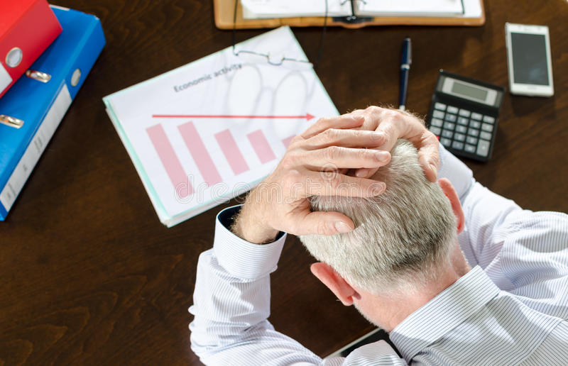 Falling down of economic activity. Despairing businessman because of the economic crisis stock photography
