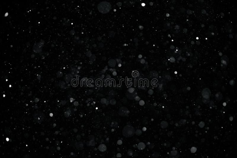 Falling down real snowflakes from left to right, calm snow, shot on black background, matte, wide angle, isolated stock images
