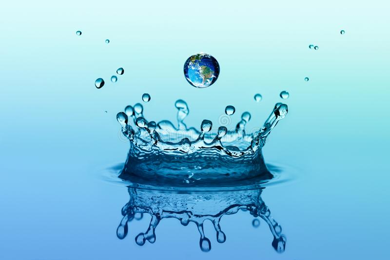 Water splash in crown shape and falling drop with earth image royalty free stock images
