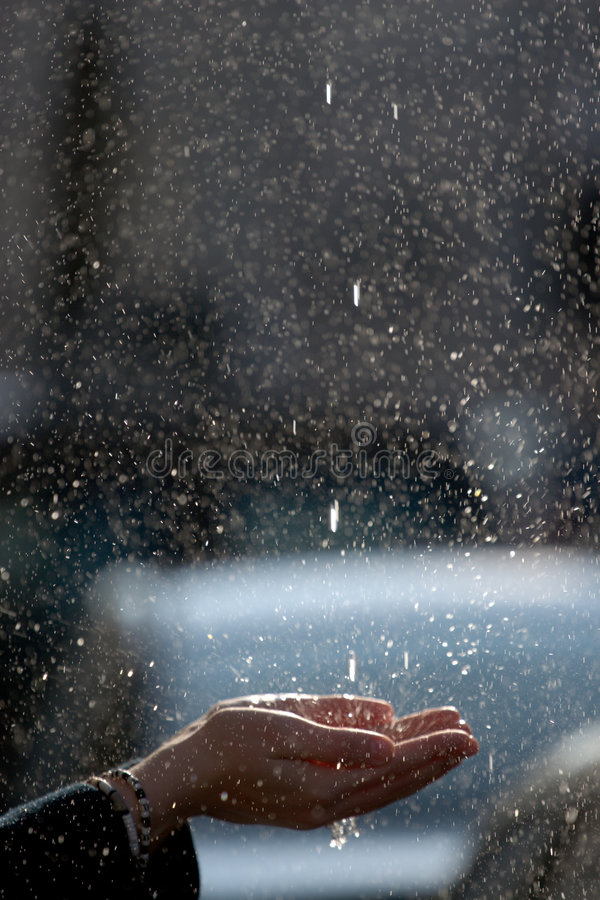 Falling droplets splashes against girl hands. On the warm spring day royalty free stock image
