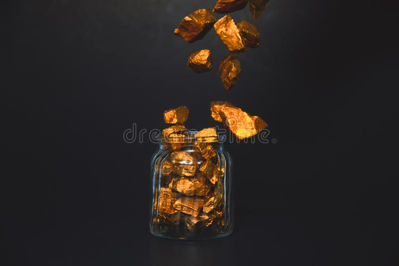 Falling gold nuggets or gold ore and glass jar in dark room. Falling gold nuggets, gold ore , precious stone or lump of golden stone and glass jar in dark room royalty free stock photography