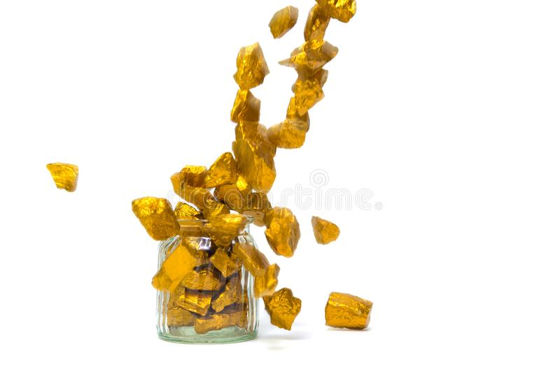 Falling gold nuggets or gold ore and glass jar isolated on white background. Falling gold nuggets, gold ore , precious stone or lump of golden stone and glass royalty free stock photography