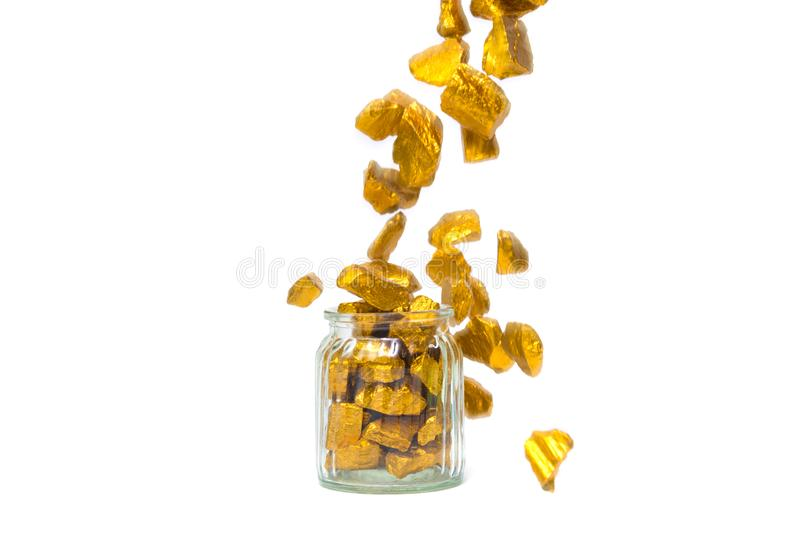 Falling gold nuggets or gold ore and glass jar isolated on white background. Falling gold nuggets, gold ore , precious stone or lump of golden stone and glass royalty free stock images