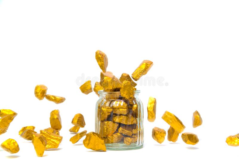 Falling gold nuggets or gold ore and glass jar isolated on white background. Falling gold nuggets, gold ore , precious stone or lump of golden stone and glass stock photography