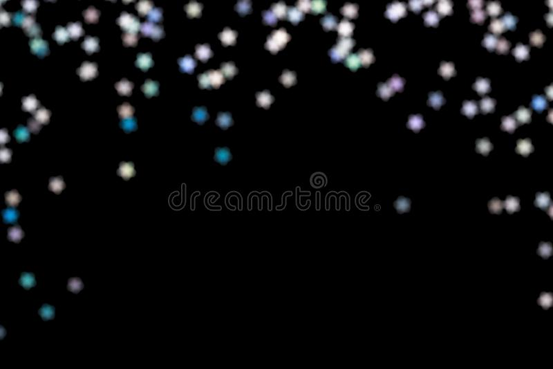 Falling Iridescent bokeh on black festive background Glowing lights frame. Falling Iridescent bokeh on black Festive holiday background. Glowing lights, overlay royalty free stock photos