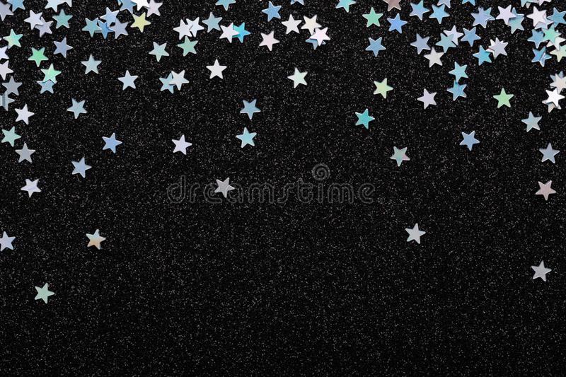 Falling Iridescent Silver stars confetti on black festive background Glowing sparkles frame. Falling Iridescent Silver stars confetti on black Festive holiday royalty free stock photo