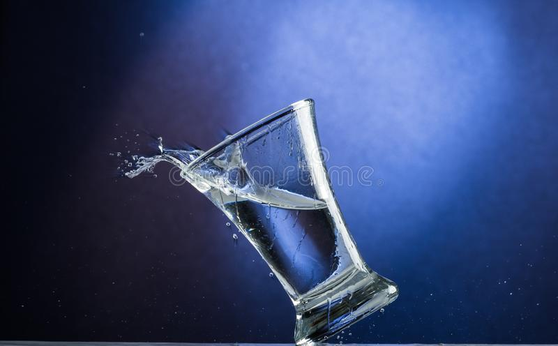 Falling and jumping glass with spilling liquid on a blue gradient background.  stock photography