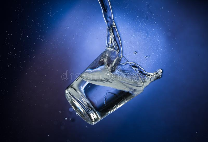 Falling and jumping glass with spilling liquid on a blue gradient background.  royalty free stock photo