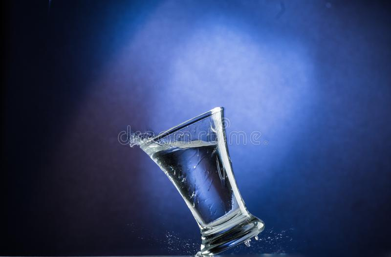 Falling and jumping glass with spilling liquid on a blue gradient background.  royalty free stock image
