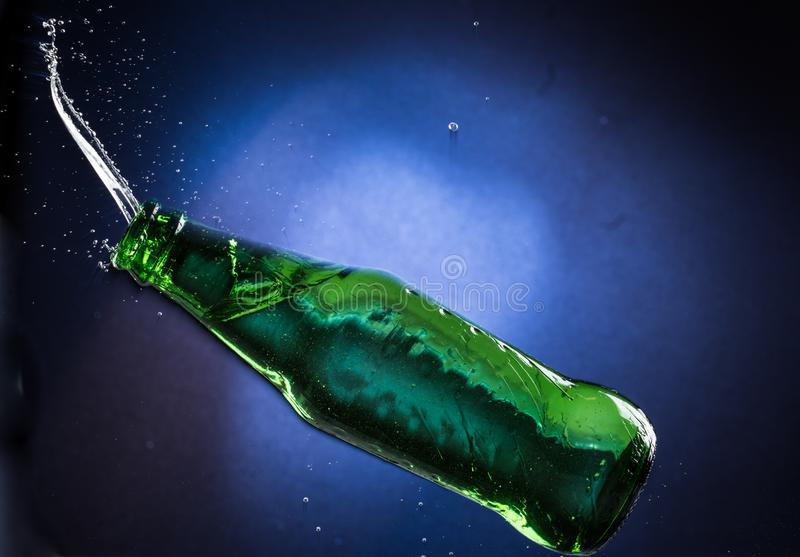 Falling and jumping green bottle with spilling liquid on a blue gradient background.  royalty free stock photos