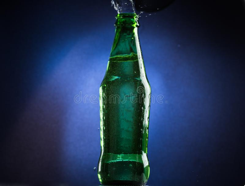 Falling and jumping green bottle with spilling liquid on a blue gradient background.  stock photo