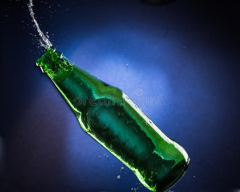 Falling and jumping green bottle with spilling liquid on a blue gradient background.  royalty free stock photo