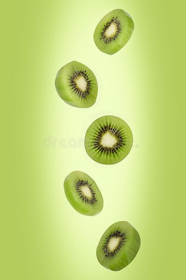 Falling kiwi isolated on green background with clipping path as package design element and advertising. Flying foods. Floating, hanging fruits in the air. Copy stock images