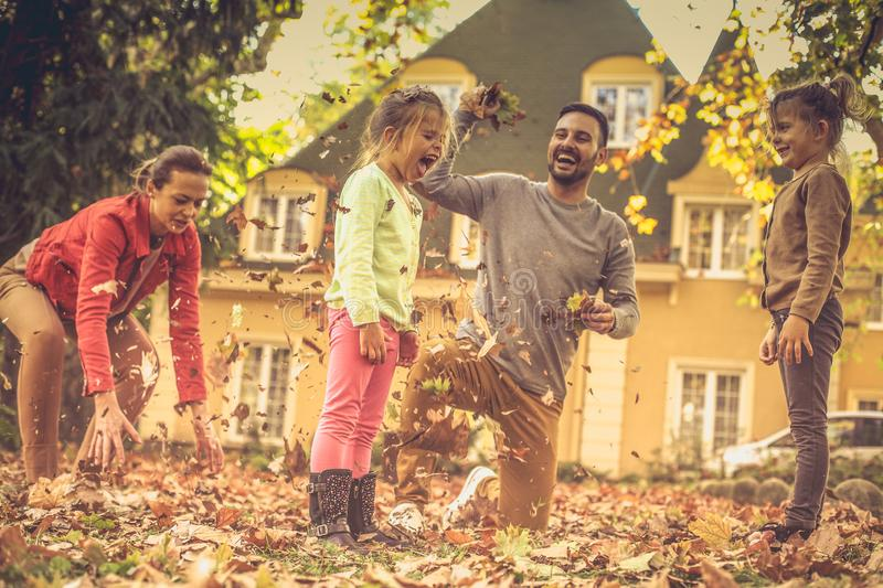 Falling leaves and my family. This autumn season is so funny. stock photography