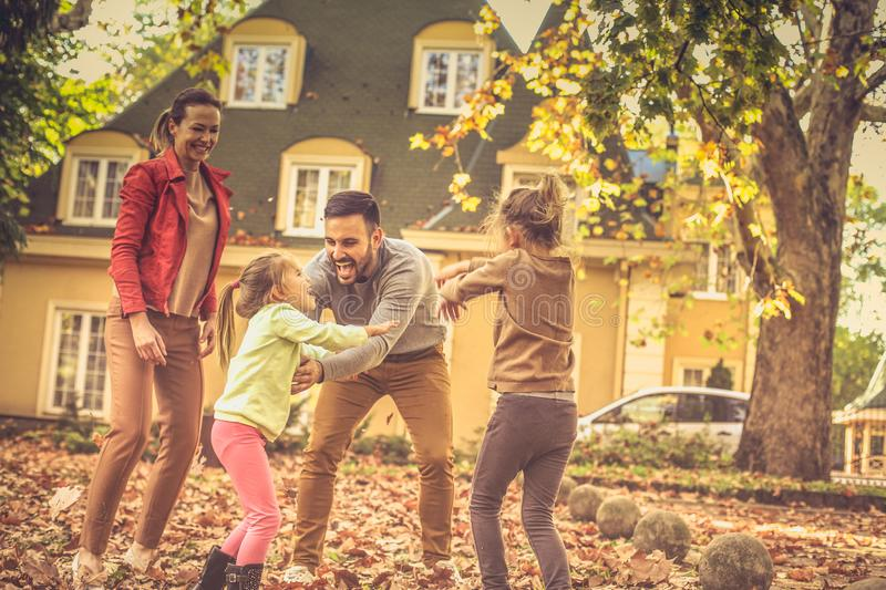 Falling leaves and my family. This autumn season is so funny. royalty free stock photo