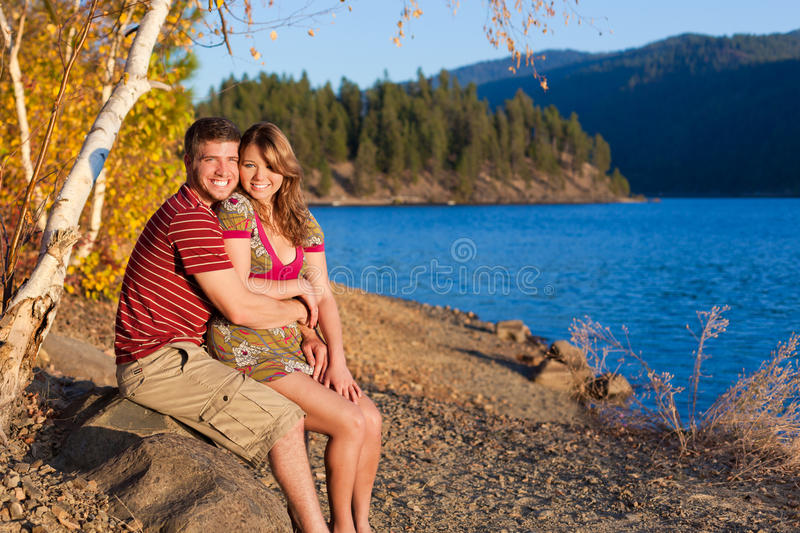 Falling in love in autumn. Young couple in love sitting by the lake enjoying the changing leaves and view of the lake