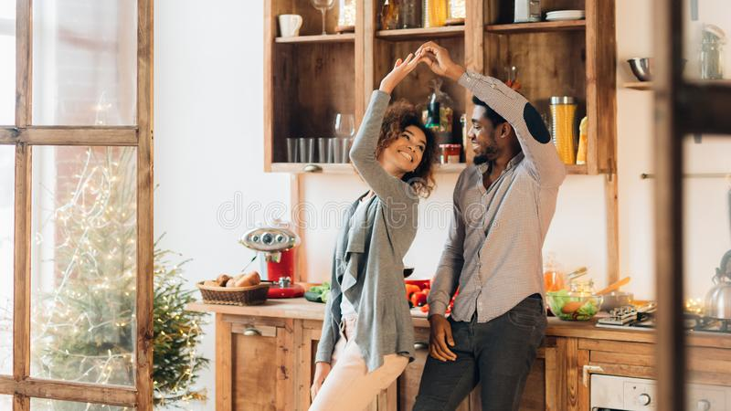 Young african-american couple dancing in kitchen, copy space royalty free stock photography