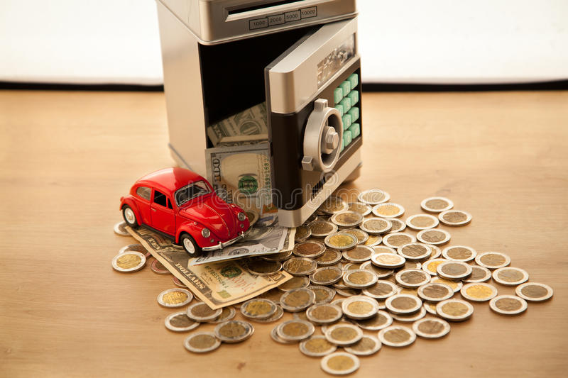 Falling money from the safe. Savings on the car. Falling money from the safe royalty free stock images