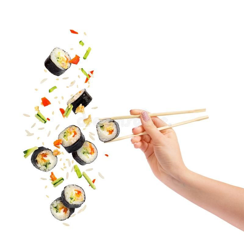 Falling pieces of sushi and sushi roll with wooden chopsticks royalty free stock image