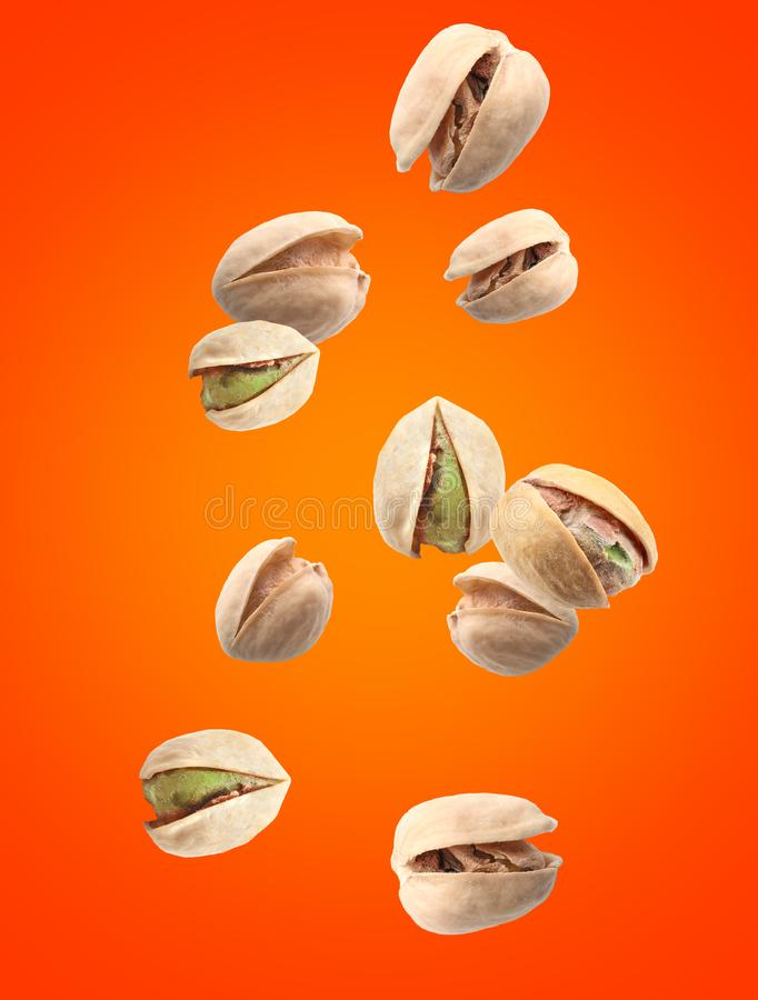 Falling pistachio nuts on color background stock images