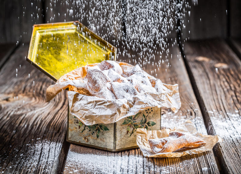 Falling powdered sugar on angel wings in box. On old wooden table stock image