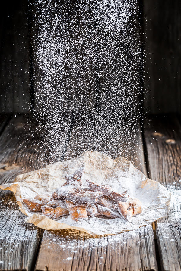 Falling powdered sugar and angel wings. On old wooden table stock images