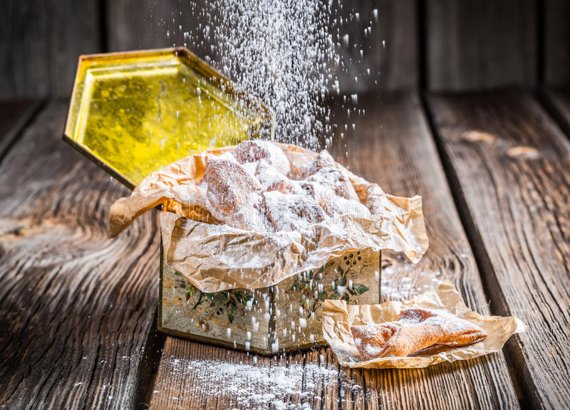 Falling powdered sugar on angel wings. On old wooden table stock photography