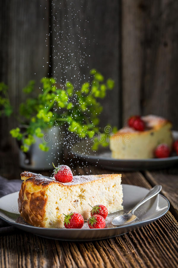 Falling powdered sugar on cheesecake with fresh strawberries royalty free stock photo