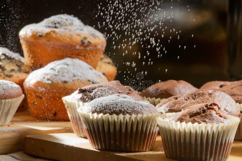 Falling powdered sugar on chocolate muffin stock photography