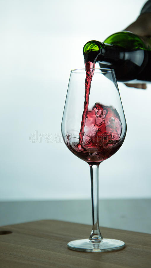 Falling red wine in glass royalty free stock photos